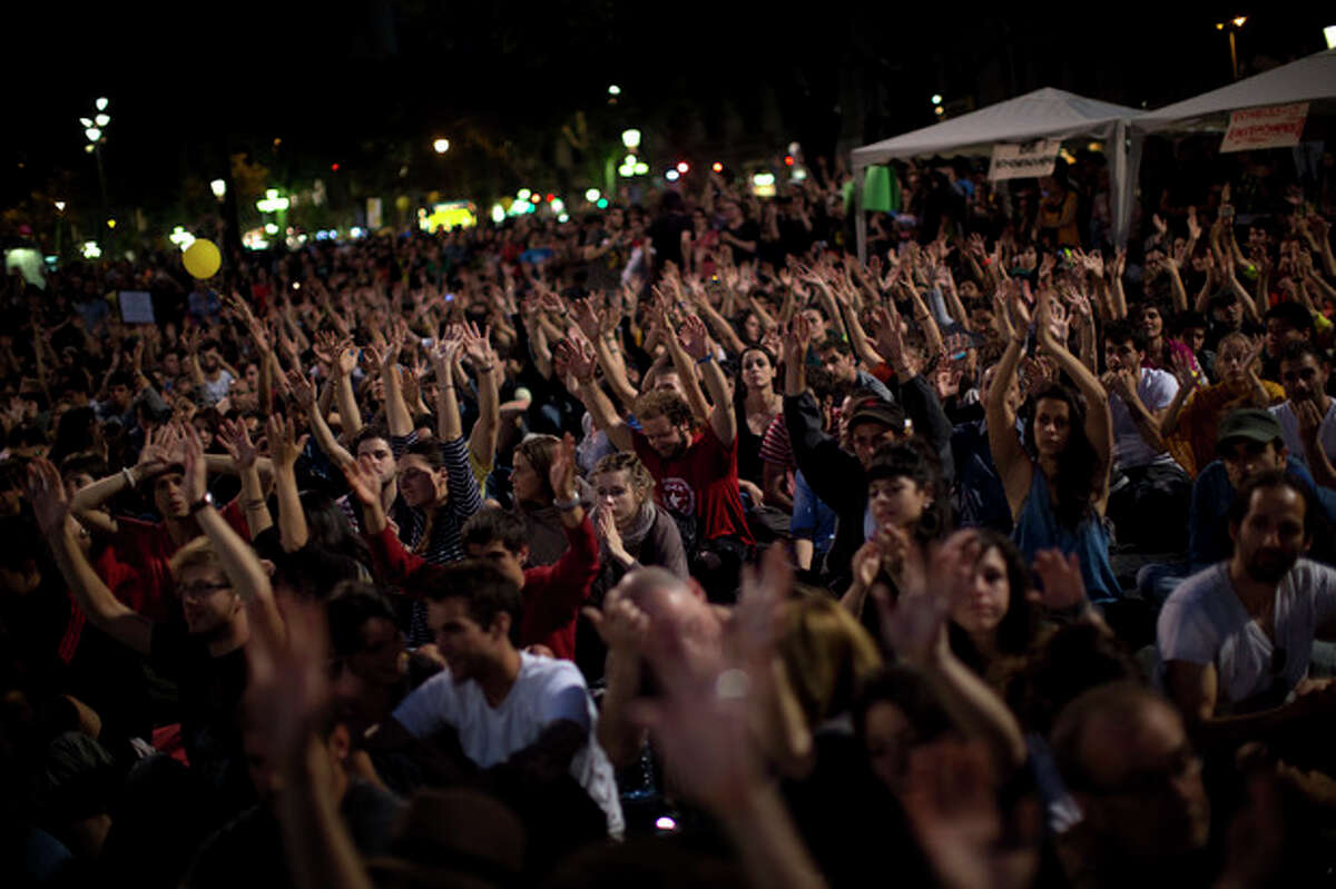 """Demonstrators rise their hands as they take part in a protest to mark the anniversary of the beginning of the """"Indignados"""" movement in Barcelona, Spain, Saturday May 12, 2012. Spanish activists angered by grim economic prospects planned nationwide demonstrations Saturday to mark the one-year anniversary of their protest movement that inspired similar groups in other countries. The protests began May 15 last year and drew hundreds of thousands of people calling themselves the Indignant Movement. The demonstrations spread across Spain and Europe as anti-austerity sentiment grew. (AP Photo/Emilio Morenatti)"""