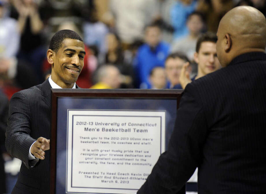 Connecticut coach Kevin Ollie, left, is presented a plaque by athletic director Warde Manuel after his team's 63-59 overtime win against Providence in an NCAA college basketball game in Storrs, Conn., Saturday, March 9, 2013. (AP Photo/Fred Beckham)