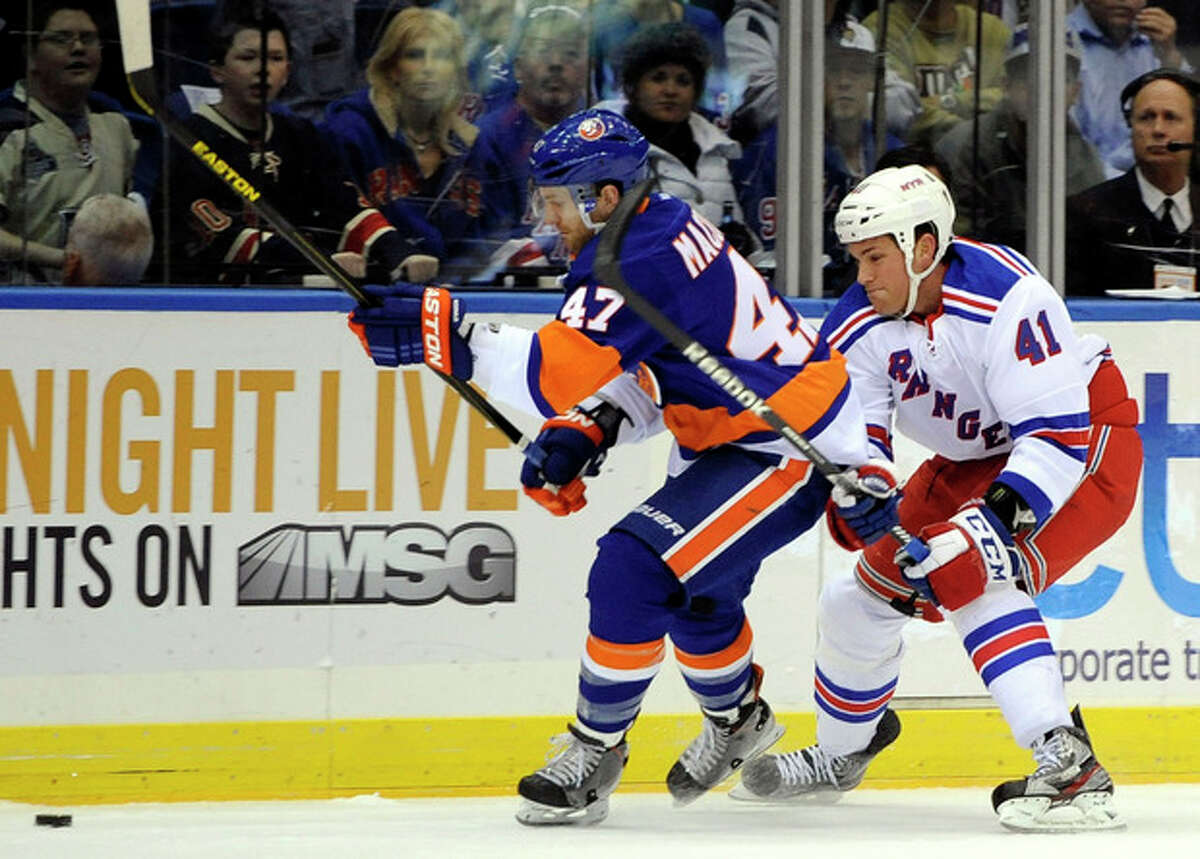 New York Islanders' Andrew MacDonald (47) and New York Rangers' Stu Bickel (41) battle for the puck in the first period of an NHL hockey game on Thursday, March 7, 2013, at Nassau Coliseum in Uniondale, N.Y. (AP Photo/Kathy Kmonicek)