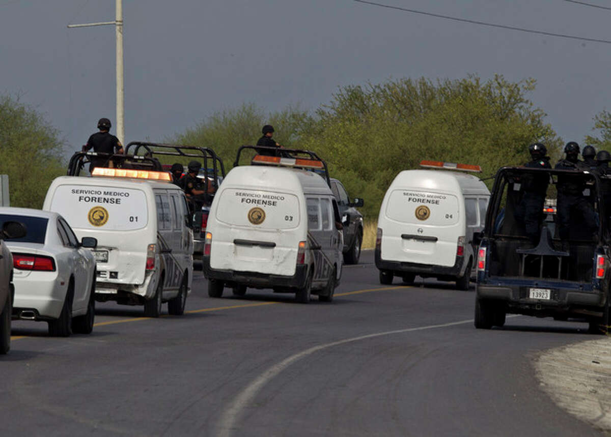 Federal police on vehicles escort the three forensic trucks where bodies were placed after dozens of bodies, some of them mutilated, were found on a highway connecting the northern Mexican metropolis of Monterrey to the U.S. border in the town of San Juan near the city of Monterrey, Mexico, Sunday, May 13, 2012. (AP Photo/Christian Palma)