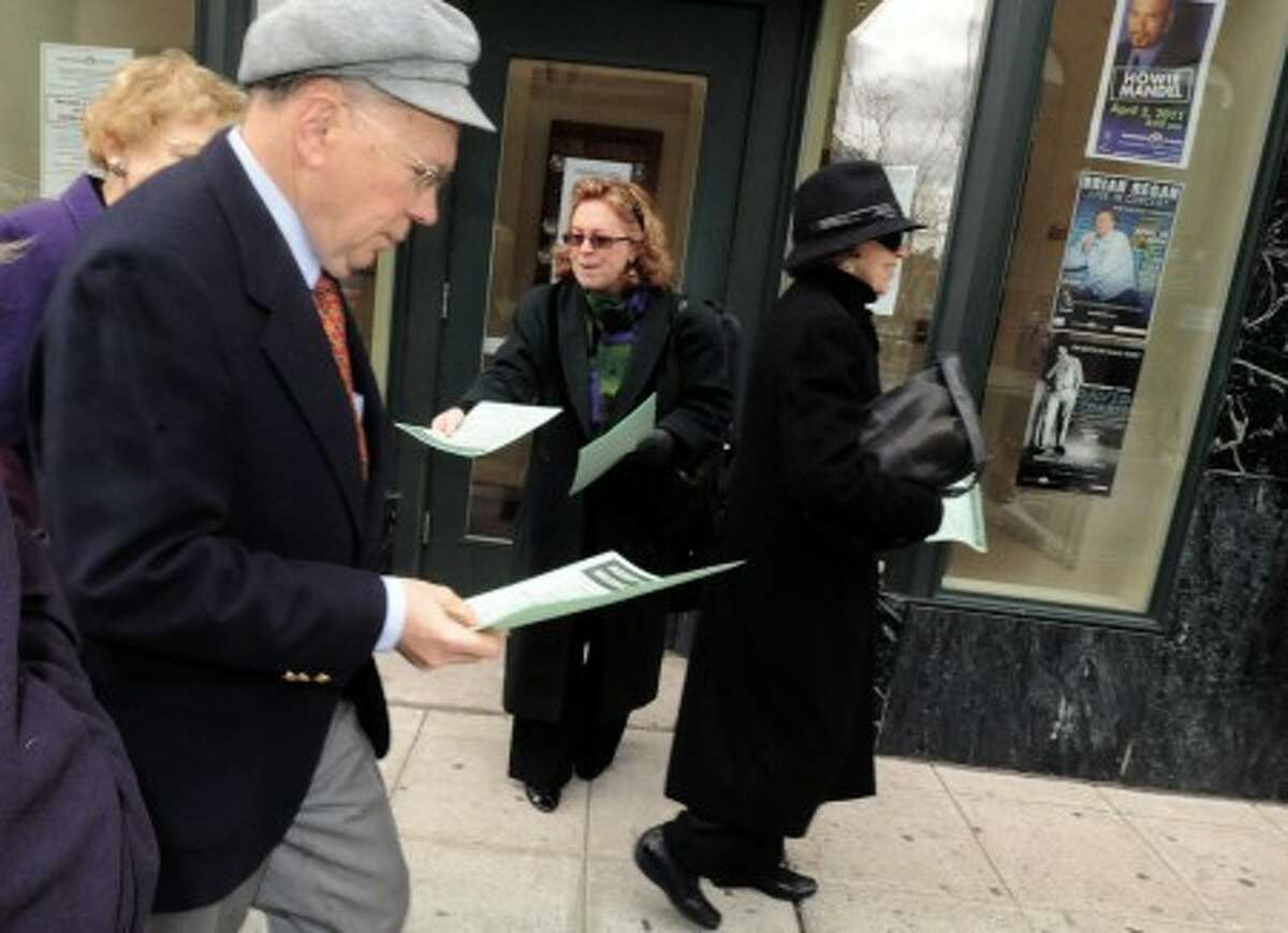 Lisa Tipton, violinist for the Stamford Symphony Orchestra hands out flyers outside the Palace Theater in Stamford Sunday where a protest was held on the proposed pay scale that they say will affect musicans. hour photo/matthew vinci