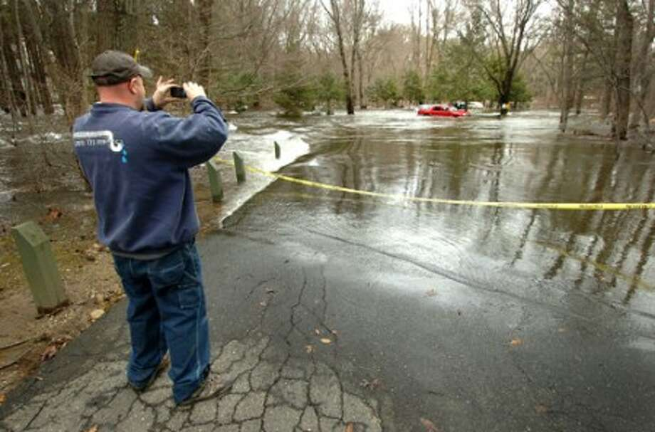 Photo/Alex von Kleydorff. Sam Wirth with Westport Plumbing stops to take a picture of a flooded parking lot after trying to make it to a clients house to pump out the basement.