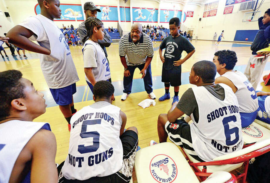 Top, Sherwood Taylor rallies his Carver Center team in their game against the Hartford YMCA during the Shoot Hoops, Not Guns basketball tournament at Brien McMahon High School Saturday. Middle, Stamford police help 5-year-old Jaden Gill from Stamford with the city basketball league, Mighty Might Basketball. Bottom, Tyrique Langley goes to the hoop. / (C)2013, The Hour Newspapers, all rights reserved