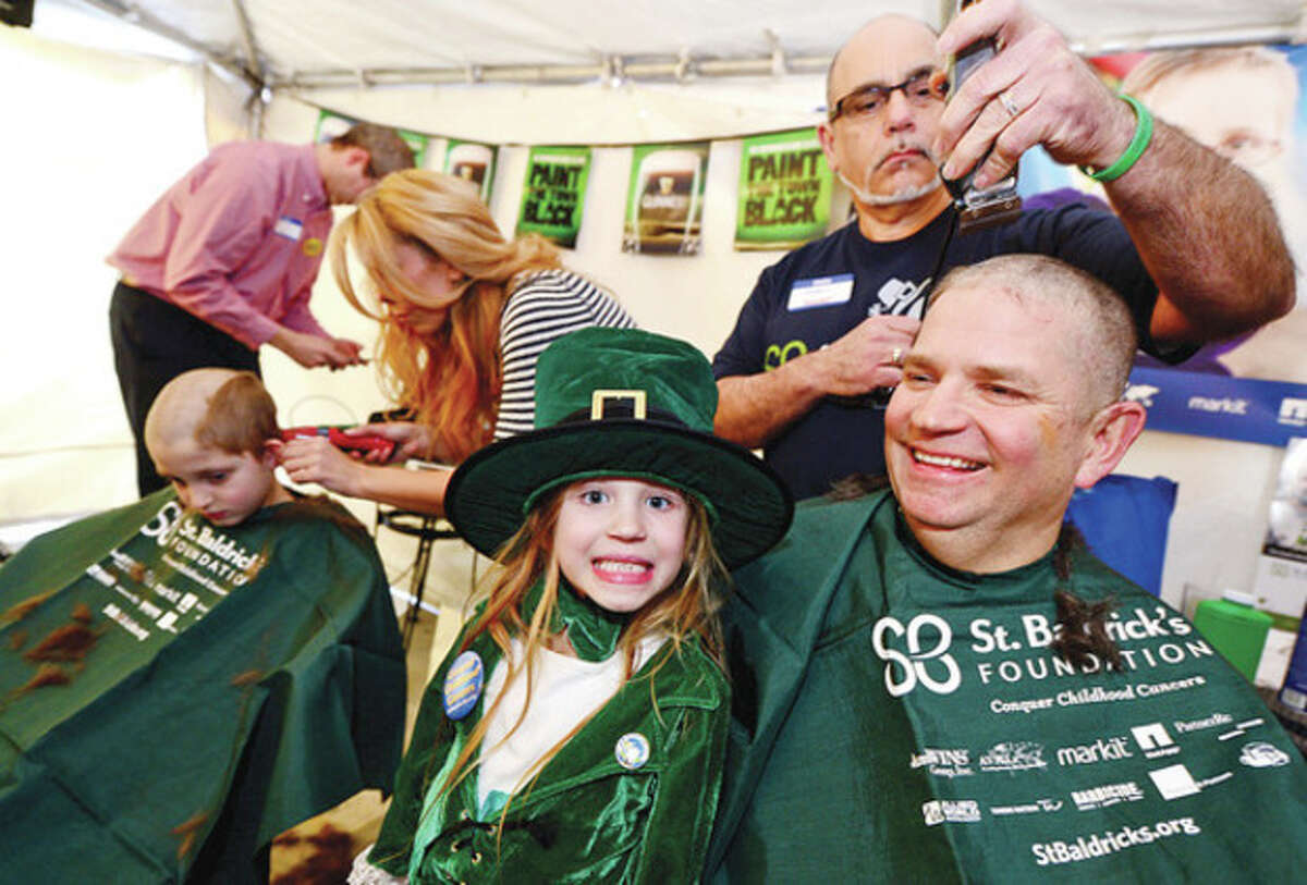 Kate Sullivan smiles with glee as her father, Kevin Sullivan, and brother, Brendan, get their heads shaved during O'Neiil's Pub annual St. Baldrick's event where volunteers shave their heads and receive pledges of financial support from their friends and family for life-saving pediatric cancer research. Hour photo / Erik Trautmann
