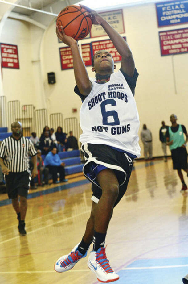 Tyrique Langley goes to the hoop against the Hartford YMCA during the Shoot Hoops Not Guns basketball tournament at Brien Mcmahon High School Saturday.Hour photo / Erik Trautmann