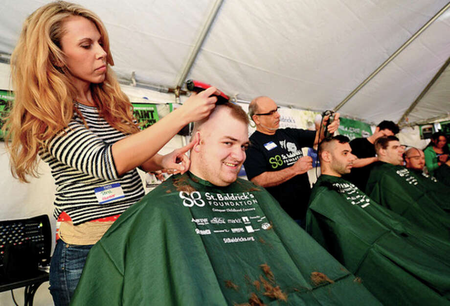 Artistic Image Salon's Dana Smith shaves the head ofFactset's Paul Lemieux during O'Neiil's Pub annual St. Baldrick's event where volunteers shave their heads and receive pledges of financial support from their friends and family for life-saving pediatric cancer research.Hour photo / Erik Trautmann / (C)2013, The Hour Newspapers, all rights reserved