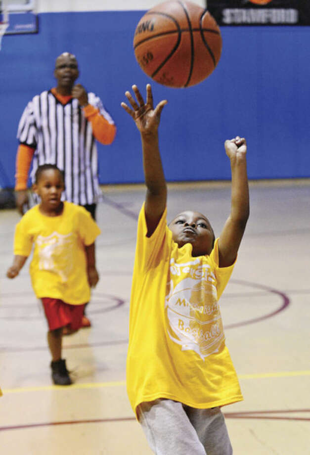 Stamford police officers help Stamford kids like 5 year old Jaden Gill with the city basketball league, Mighty Might Basketball.Hour photo / Erik Trautmann