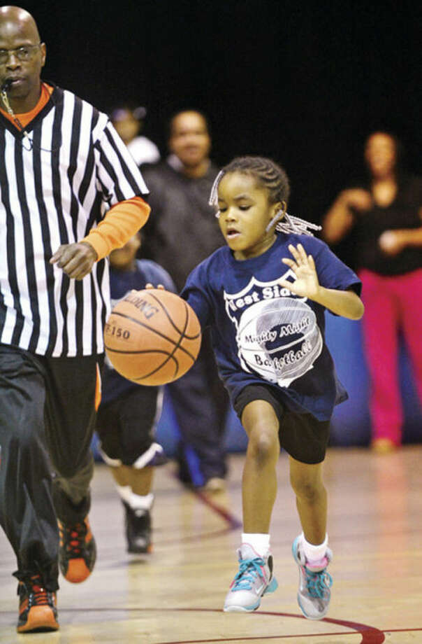 Stamford police officers help Stamford kids like 6 year old Madison Watts with the city basketball league, Mighty Might Basketball.Hour photo / Erik Trautmann