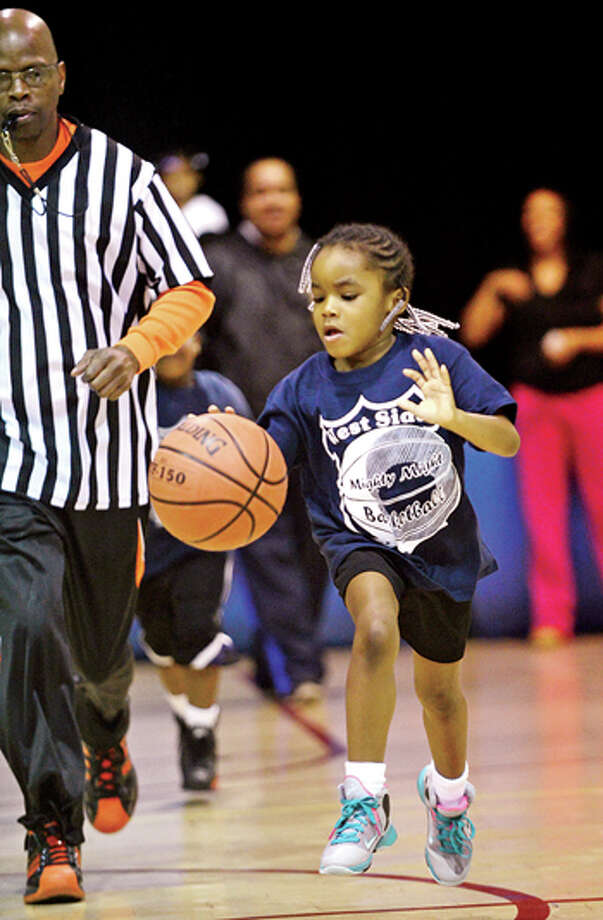 Stamford police officers help Stamford kids like 6 year old Madison Watts with the city basketball league, Mighty Might Basketball. Hour photo / Erik Trautmann / (C)2013, The Hour Newspapers, all rights reserved