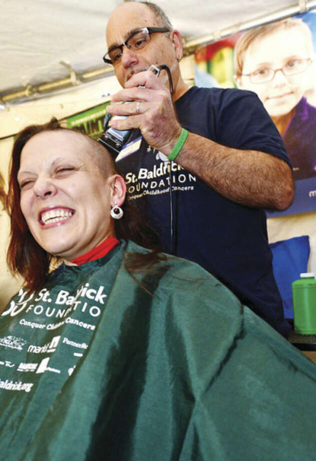 Mane St Salon's Victor Lacanfora shaves the head of Jennifer Amon during O'Neiil's Pub annual St. Baldrick's event where volunteers shave their heads and receive pledges of financial support from their friends and family for life-saving pediatric cancer research.Hour photo / Erik Trautmann