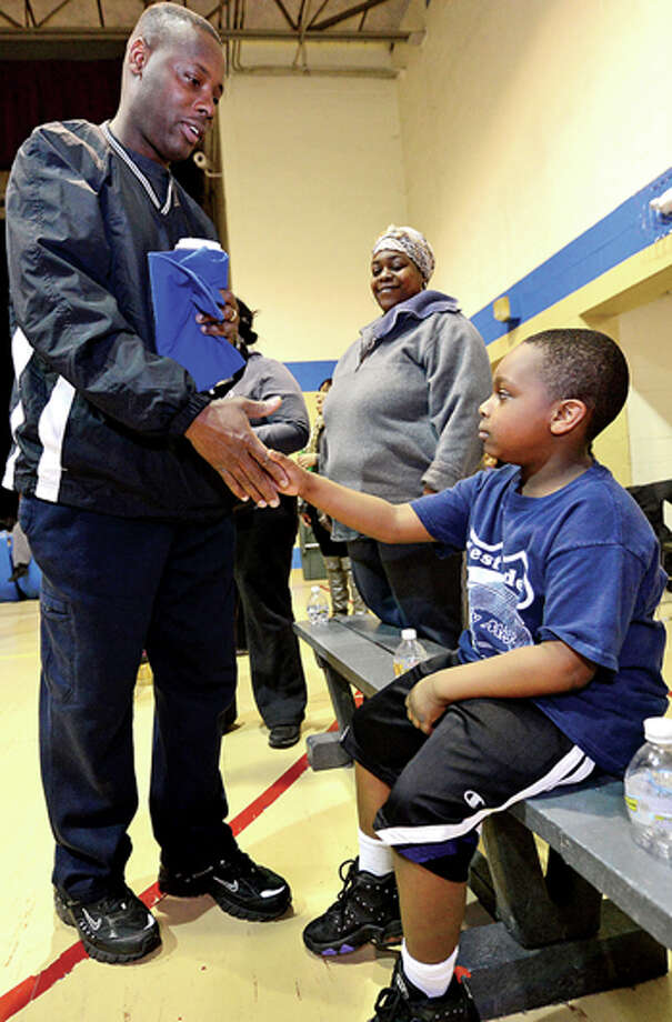 Stamford police officer Jerry Junes help Stamford kids like 5 year old Troy Baker with the city basketball league, Mighty Might Basketball. Hour photo / Erik Trautmann / (C)2013, The Hour Newspapers, all rights reserved