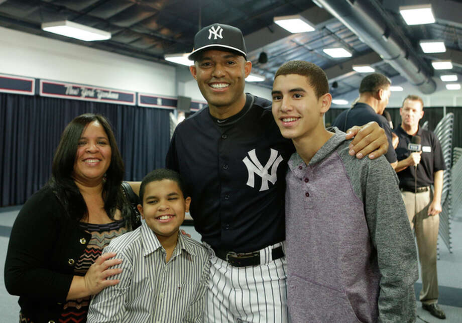 New York Yankees pitcher Mariano Rivera, who holds baseball's all-time saves record, poses for a photograph with his wife Clara, sons Jaziel, left, and Jafet, right, after announcing his plans to retire at the end of the 2013 season during a news conference at Steinbrenner Field Saturday, March 9, 2013 in Tampa, Fla. (AP Photo/Kathy Willens) / AP