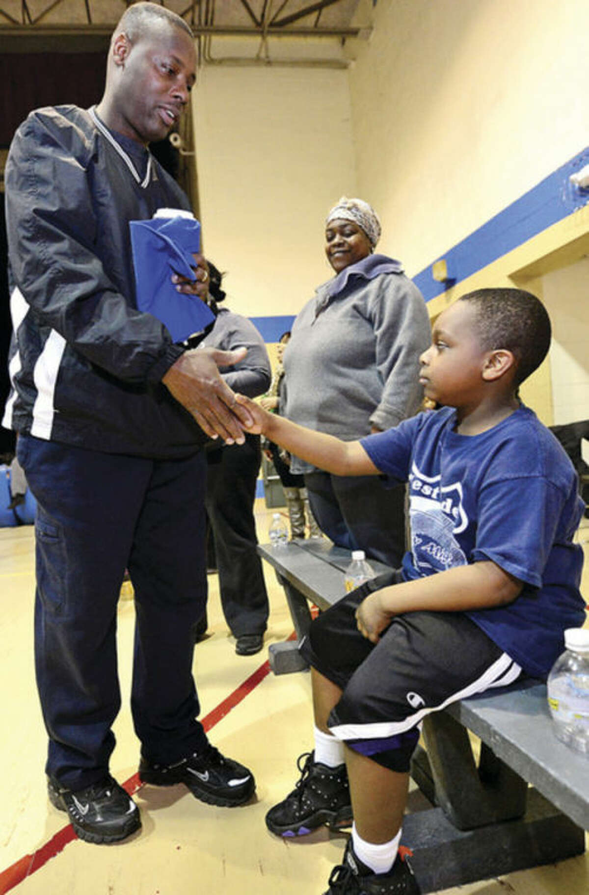 Stamford police officer Jerry Junes help Stamford kids like 5 year old Troy Baker with the city basketball league, Mighty Might Basketball. Hour photo / Erik Trautmann