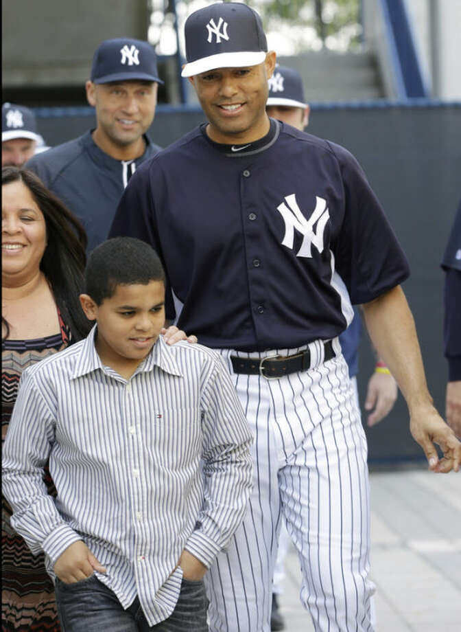 New York Yankees pitcher Mariano Rivera, who holds baseball's all-time saves record, walks with his wife Clara, far left, and his son Jaziel, followed by Yankees shortstop Derek Jeter, before announcing his plans to retire at the end of the 2013 season at a news conference at Steinbrenner Field Saturday, March 9, 2013 in Tampa, Fla. (AP Photo/Kathy Willens)