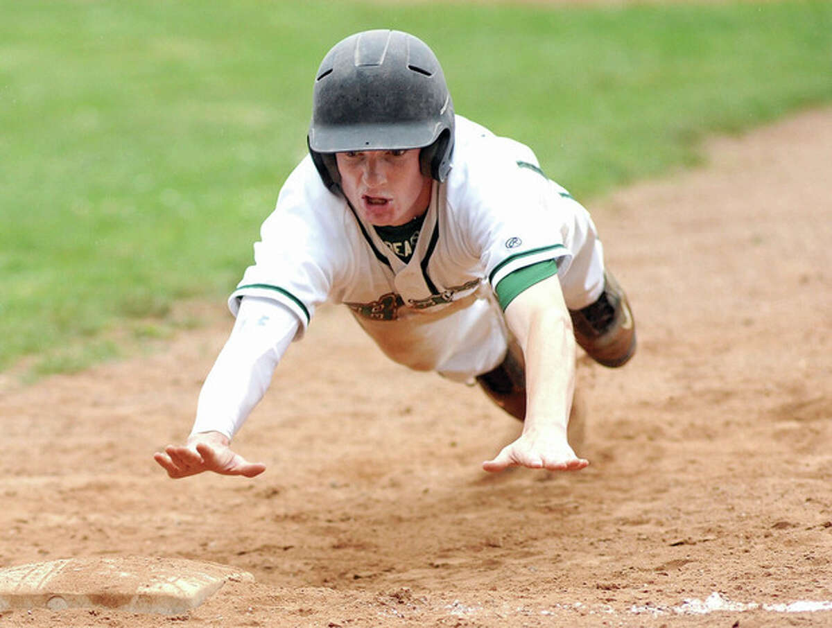 Hour photo/John Nash Norwalk's Ryan Halloran dives back toward first base on a pick off attempt during Monday's game against Westhill at Malmquist Field. The visiting Vikings left town with a 9-2 victory in hand.