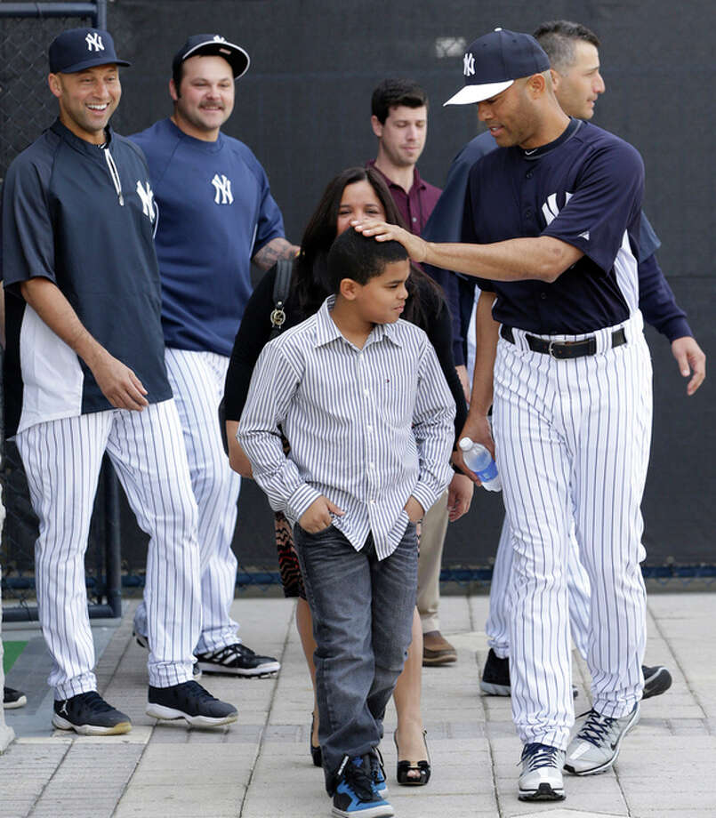 New York Yankees shortstop Derek Jeter, far left, and reliever Joba Chamberlain, second from left, watch as pitcher Mariano Rivera, far right, pats his son Jaziel on the head before a news conference announcing his plans to retire at the end of the 2013 season at Steinbrenner Field Saturday, March 9, 2013, in Tampa, Fla. Yankees pitcher Andy Pettitte is behind Rivera. Rivera holds baseball's all-time saves leader. (AP Photo/Kathy Willens) / AP