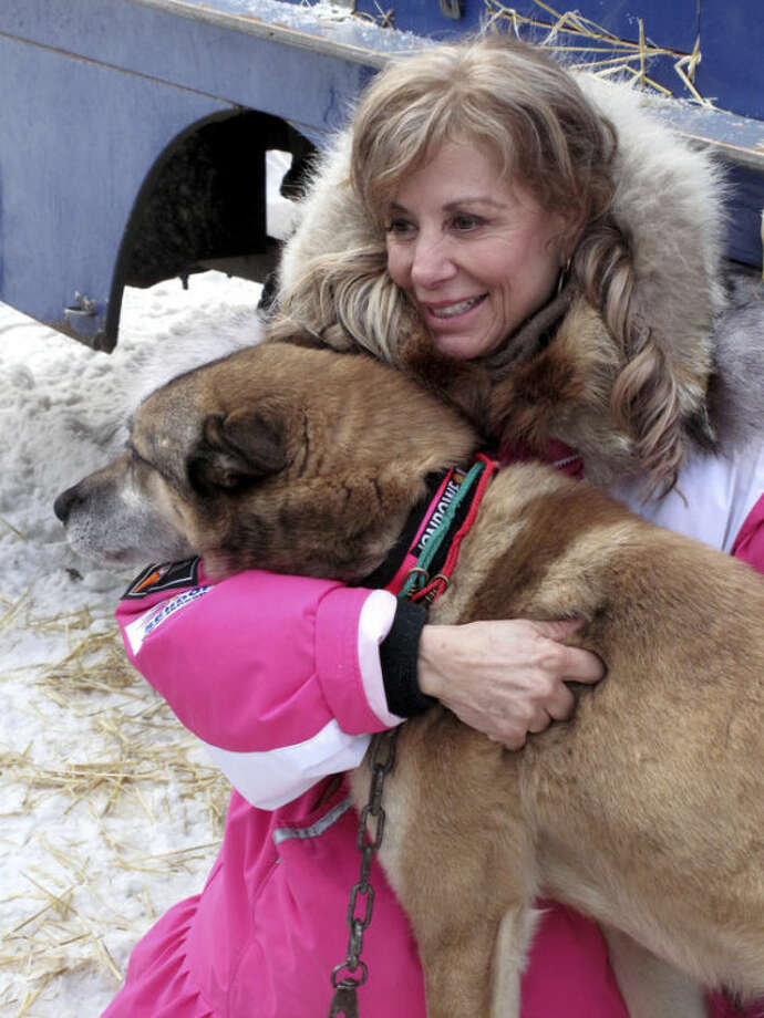 Veteran musher DeeDee Jonrowe poses with a member of her team at the ceremonial start of the Iditarod Trail Sled Dog Race Saturday, March 2, 2013, in Anchorage, Alaska. The competitive portion of the 1,000-mile race is scheduled to begin Sunday in Willow, 50 miles to the north. (AP Photo/Rachel D'Oro)