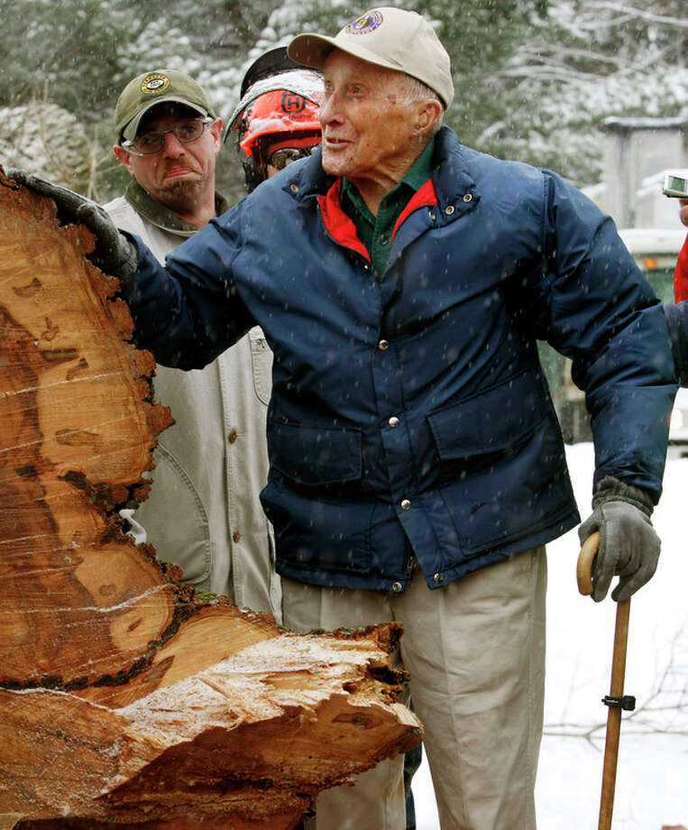 "FILE - In this Jan. 19, 2010 file photo, Frank Knight puts his hand on New England's tallest elm tree, known as ""Herbie,"" after it succumbed to Dutch elm disease and was cut down in Yarmouth, Maine. Knight, who took care of the tree for five decades while working as the Yarmouth tree warden, died in Scarborough, Maine, Monday, May 14, 2012. He was 103. (AP Photo/Pat Wellenbach, File) / AP2010"