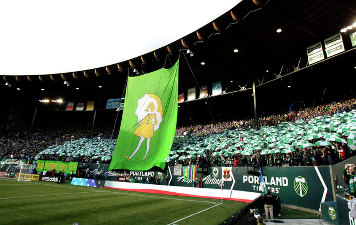 Members of the Portland Timbers Army hold up umbrellas as a giant banner is unveiled before during the first half of an MLS soccer game against the New York Red Bulls in Portland, Ore., Sunday, March 3, 2013. (AP Photo/Don Ryan)