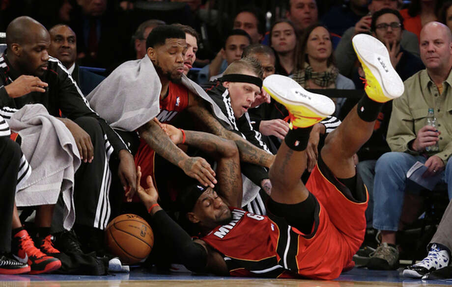 Miami Heat forward LeBron James (6) falls into the bench during the first half of an NBA basketball game against The New York Knicks at Madison Square Garden in New York, Sunday, March 3, 2013. (AP Photo/Kathy Willens) / AP