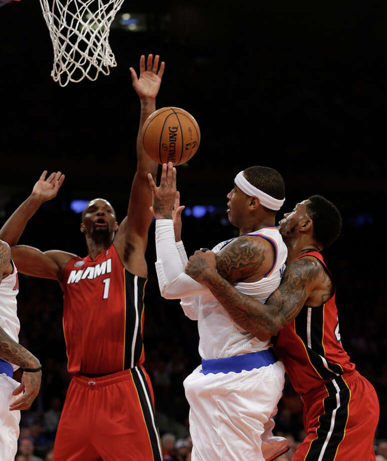 Miami Heat forward Udonis Haslem, right, holds New York Knicks forward Carmelo Anthony, center, as Heat center Chris Bosh (1) tries to block Anthony's shot during the first half of their an basketball game at Madison Square Garden in New York, Sunday, March 3, 2013. A foul was called on Haslem. (AP Photo/Kathy Willens) / AP