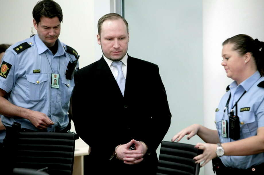 Anders Behring Breivik between 2 police officers prior to taking his seat after a break in the courtroom in Oslo Tuesday morning May 15, 2012. When the trial opened, the self-styled anti-Muslim crusader pleaded innocent to terror charges _ even though he admitted to the facts of the case _ saying he didn't recognize the authority of the court. (AP Photo/Stian Lysberg Solum, Pool) / POOL NTB scanpix
