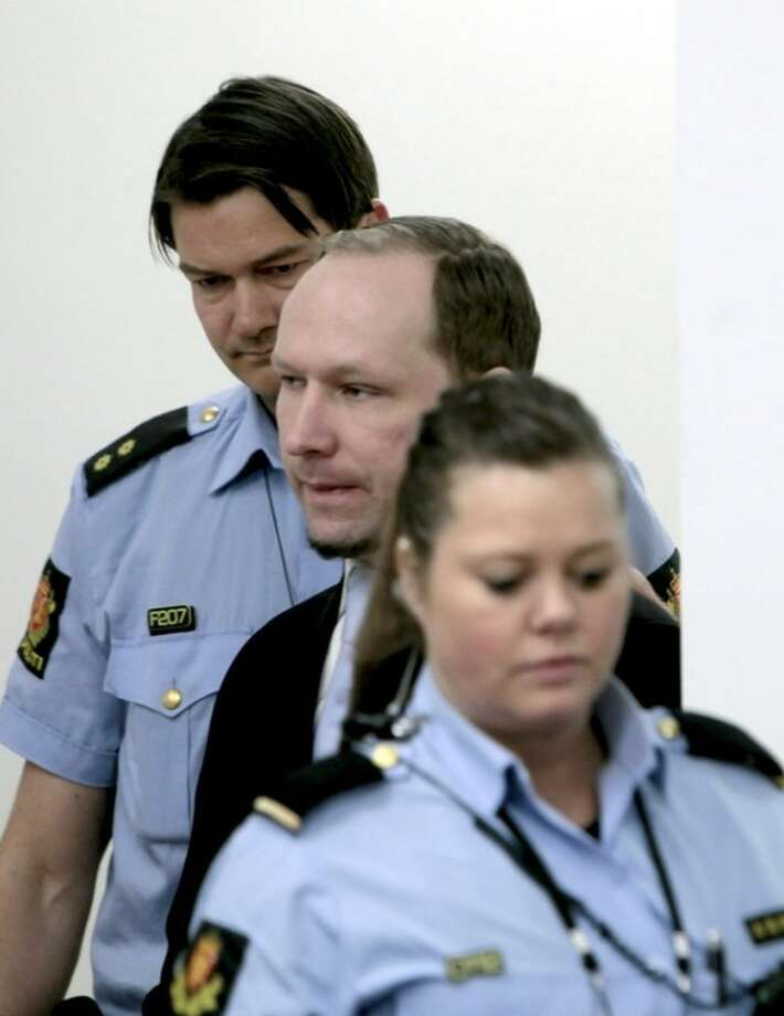 Anders Behring Breivik between 2 police officers prior to taking his seat after a break in the courtroom in Oslo Tuesday morning May 15, 2012. When the trial opened, the self-styled anti-Muslim crusader pleaded innocent to terror charges _ even though he admitted to the facts of the case _ saying he didn't recognize the authority of the court. (AP Photo/Stian Lysberg Solum, Pool)