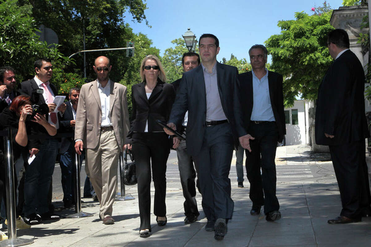 Greek leader of Coalition of the Radical Left Party SYRIZA Alexis Tsipras, front, arrives at the presidential palace for a meeting with President Karolos Papoulias, in Athens, on Tuesday, May 15, 2012. Greece's president is to meet the leaders of five political parties, broadening talks to try and form a coalition government and end a nine-day deadlock in the crisis-hit country. (AP Photo/Petros Giannakouris)