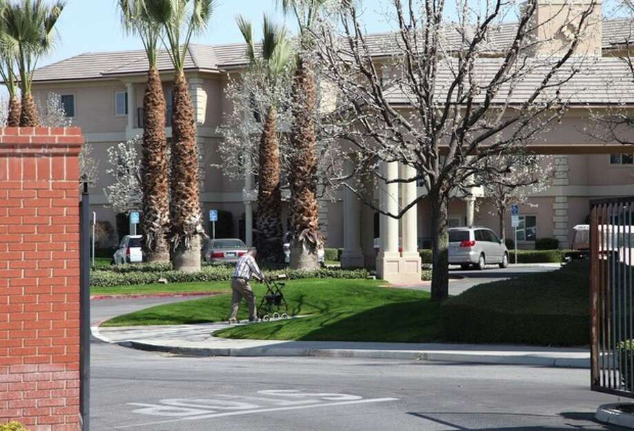 "A man walks near the main gate of Glenwood Gardens in Bakersfield, Calif., Monday March 4, 2013, where an elderly woman died after a nurse refused to perform CPR on her last week. The central California retirement home is defending one of its nurses who refused pleas by a 911 operator to perform CPR on an elderly woman, who later died. ""Is there anybody that's willing to help this lady and not let her die,"" dispatcher Tracey Halvorson says on a 911 tape released by the Bakersfield Fire Department aired by several media outlets. (AP Photo/Gosia Wozniacka) / AP"