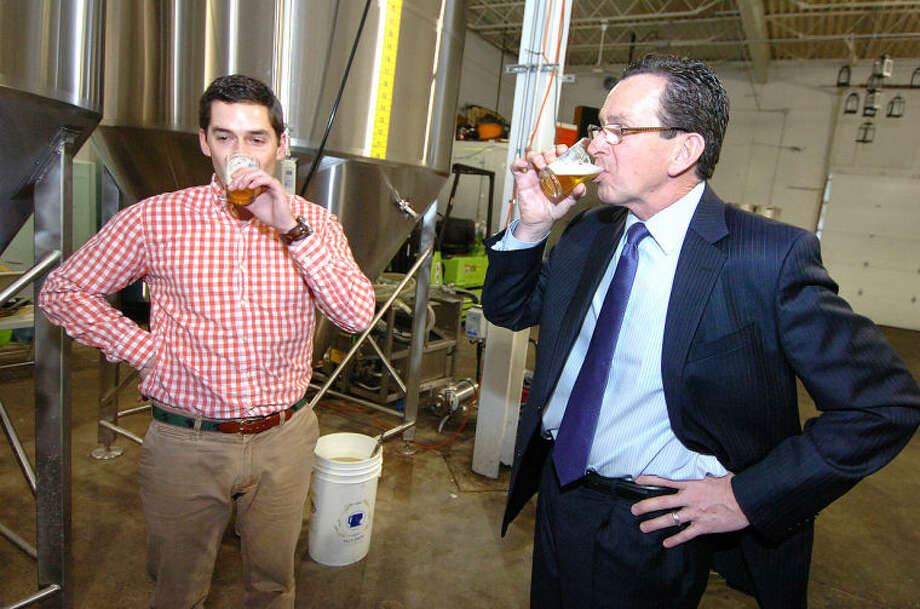 Hour Photo/ Alex von Kleydorff. Gov. Dan Malloy trys an Ale from the Fermentation tank with Owner and Chief Beer Philosopher Conor Horrigian at Half Full Brewery