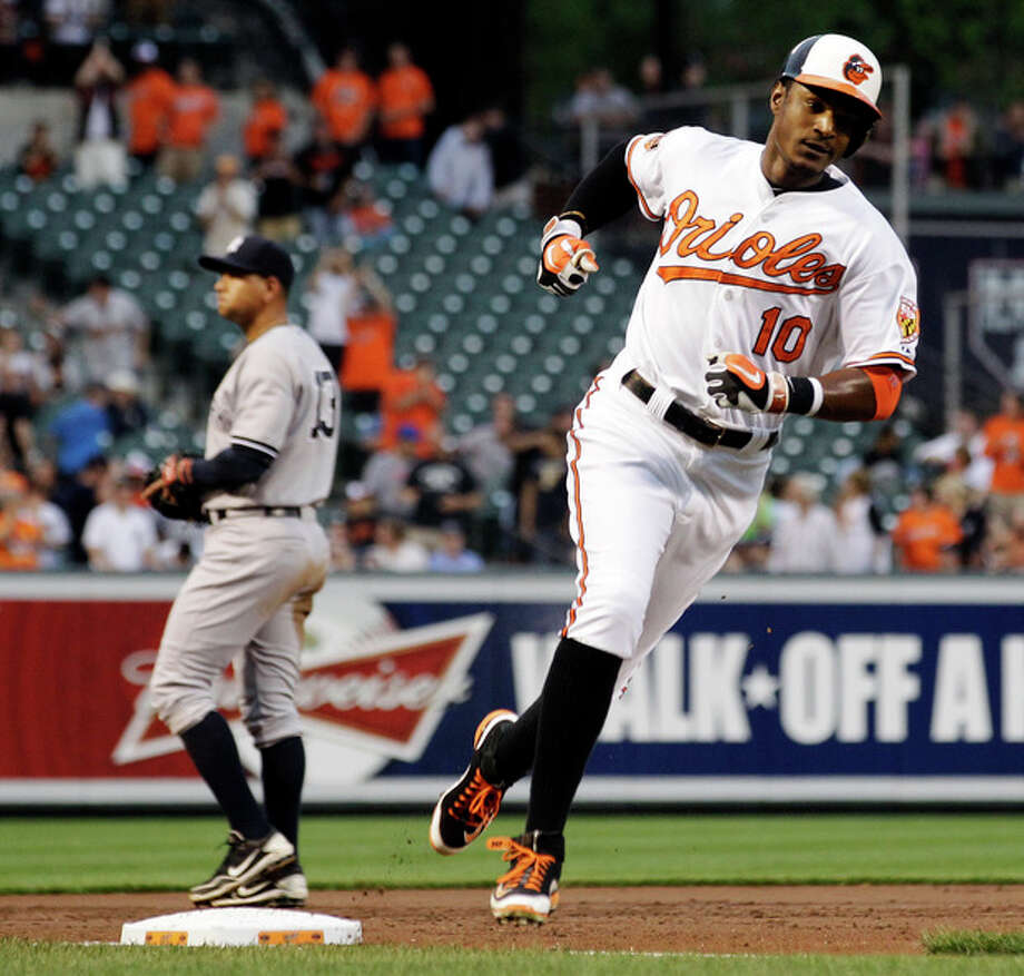 Baltimore Orioles' Adam Jones (10) rounds third base past New York Yankees third baseman Alex Rodriguez after hitting a solo home run in the second inning of a baseball game in Baltimore, Tuesday, May 15, 2012. (AP Photo/Patrick Semansky) / AP
