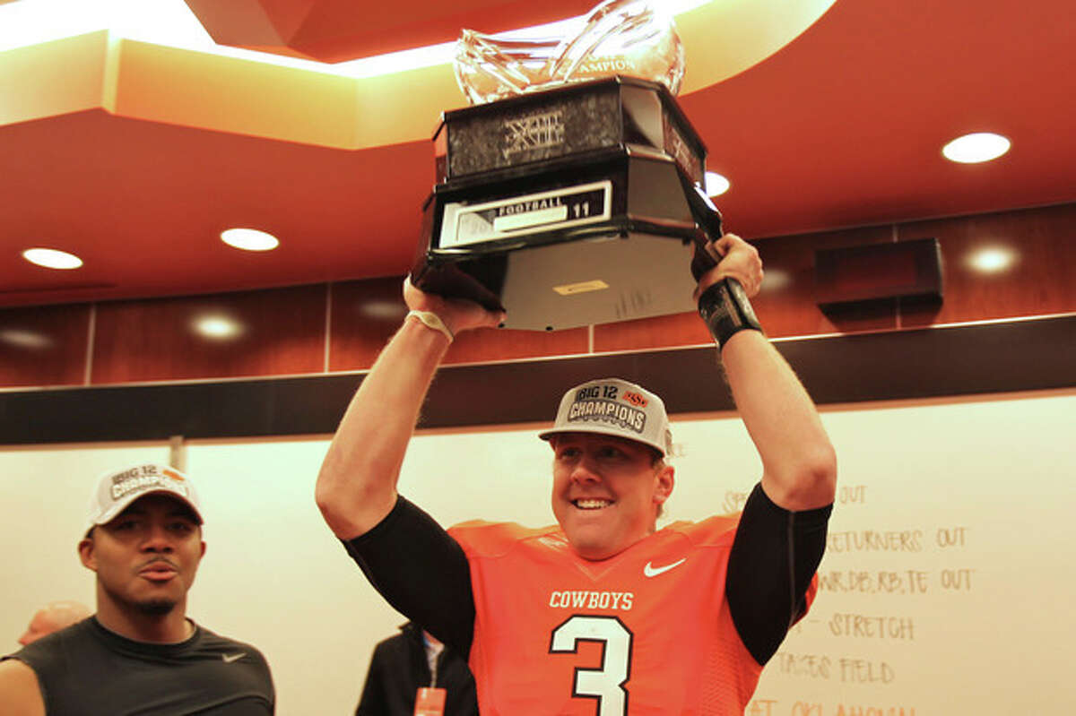 Brandon Weeden holds the Big 12 championship trophy aloft after the presentation in the Cowboys locker room Saturday Dec. 3, 2011. The Cowboys snapped an eight-game losing streak and won their first outright conference title since 1948 in the three-team Missouri Valley. (AP Photo/Oklahoma State University)