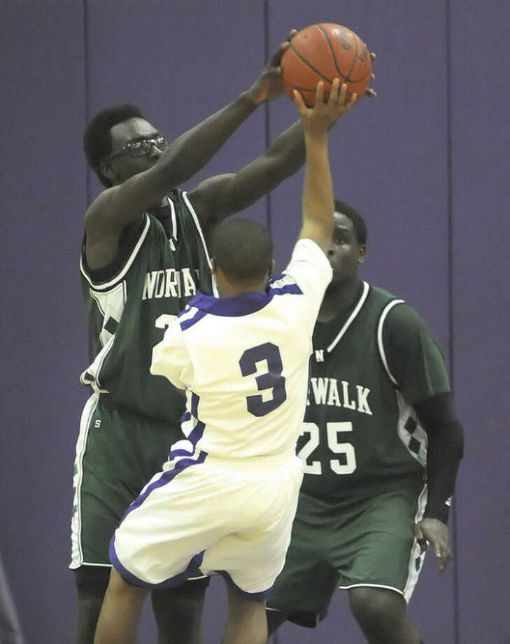 Hour photo/John NashNorwalk's Roy Kane Jr., left, blocks a shot by Westhill's CJ Donaldson (3) as teammate Saaed Soulemane looks on during the fourth quarter of Monday's Class LL first round playoff game in Stamford. The Vikings beat the Bears, 60-50.