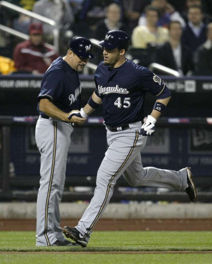 Milwaukee Brewers third base coach Ed Sedar congratulates Travis Ishikawa (45) as he rounds the bases on his solo home run off New York Mets pitcher Dillon Gee during the fifth inning of their baseball game at Citi Field in New York, Tuesday, May 15, 2012. (AP Photo/Kathy Willens)
