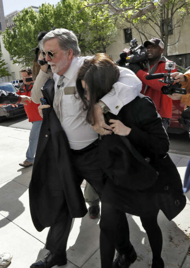 Casey Anthony is protected from the media by her attorney Cheney Mason as she arrives at the United States Courthouse for a bankruptcy hearing Monday, March 4, 2013, in Tampa, Fla. Casey has not been seen in public since being acquitted in 2011 of murdering her two-year-old daughter Caylee. (AP Photo/Chris O'Meara)