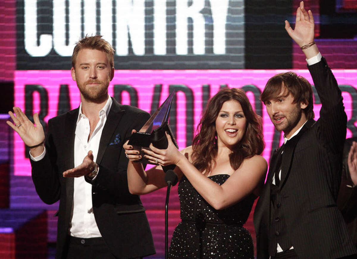 FILE - In a Nov. 20, 2011, file photo Lady Antebellum musical group members from left, Charles Kelley, Hillary Scott and Dave Haywood, accept the award for country band, duo or group at the 39th Annual American Music Awards on in Los Angeles. Grammy-winning Lady Antebellum is scheduled to perform Wednesday night, May 16, 2012, at the KFC Yum Center in Louisville, Ky., to raise money for rebuilding Henryville, Ind., about 20 miles to the north. (AP Photo/Matt Sayles, File)