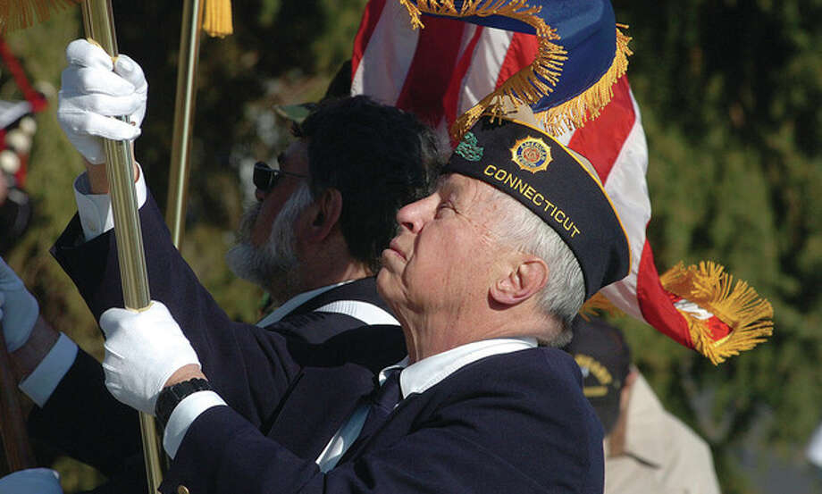Hour Photo/ Alex von Kleydorff. Alex Ruskewich with American Legion Post 86 in Wilton holds the POW-MIA flag in strong winds as part of the Color Guard at Veterans Day ceremony / 2011 The Hour Newspapers