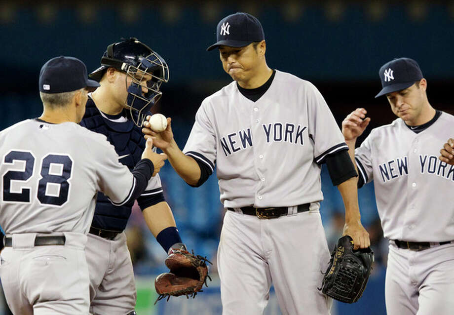 New York Yankees catcher Russell Martin, second from left, and shortstop Jason Nix, right, watch as starting pitcher Hiroki Kuroda, center, is pulled from the game by manager Joe Girardi (28) during the sixth inning of a baseball game against the Toronto Blue Jays in Toronto, Wednesday, May 16, 2012. (AP Photo/The Canadian Press, Frank Gunn) / The Canadian Press