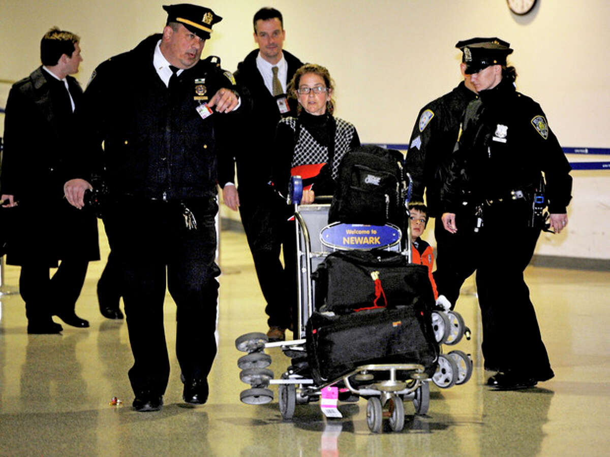 Lori Berenson, center, arrives from Lima, Peru with her son Salvador Apari at Newark Liberty International Airport, Tuesday, Dec. 20, 2011 in Newark, New Jersey. Berenson, who was convicted of aiding Peruvian guerrillas and served 15 years before she was paroled last year, said she fully intended to return to Peru by the court-ordered deadline of Jan. 11. (AP Photo/Henny Ray Abrams)