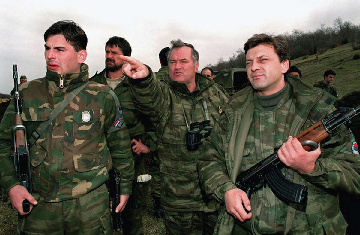 """FILE - In this April 16, 1994 photo, Bosnian Serb army commander-in-chief Col. General Ratko Mladic, center, observes Bosnian government forces positions in Gorazde, eastern Bosnia, surrounded by his bodyguards. The indictment against Ratko Mladic, who went on trial Wednesday May 16, 2012 at the U.N. war crimes tribunal in the Hague, Netherlands, holds the former Bosnian Serb army commander """"individually criminally responsible for planning, instigating, ordering and/or aiding and abetting the crimes charged in this indictment."""" Mladic is charged with 11 counts of genocide, crimes against humanity and violations of the laws and customs of war. (AP Photo/Emil Vas)"""