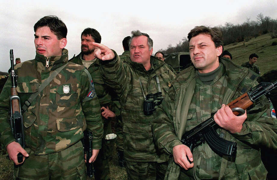 """FILE - In this April 16, 1994 photo, Bosnian Serb army commander-in-chief Col. General Ratko Mladic, center, observes Bosnian government forces positions in Gorazde, eastern Bosnia, surrounded by his bodyguards. The indictment against Ratko Mladic, who went on trial Wednesday May 16, 2012 at the U.N. war crimes tribunal in the Hague, Netherlands, holds the former Bosnian Serb army commander """"individually criminally responsible for planning, instigating, ordering and/or aiding and abetting the crimes charged in this indictment."""" Mladic is charged with 11 counts of genocide, crimes against humanity and violations of the laws and customs of war. (AP Photo/Emil Vas) / AP"""