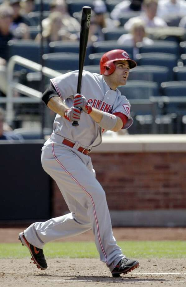 Cincinnati Reds' Joey Votto follows through with a single off New York Mets starting pitcher R.A. Dickey during the sixth inning of a baseball game at Citi Field in New York, Thursday, May 17, 2012. Votto hit a solo home run in the fourth inning off Dickey. (AP Photo/Kathy Willens)