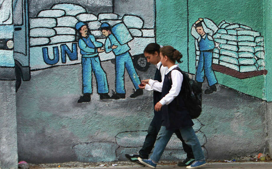 Palestinian school girls walk past a graffiti on a wall depicting UN humanitarian aid supplies, in Gaza City, Monday, Oct. 31, 2011. Palestine became a full member of the U.N. cultural and educational agency Monday, in a highly divisive move that the United States and other opponents say could harm renewed Mideast peace efforts. (AP Photo/Adel Hana) / AP