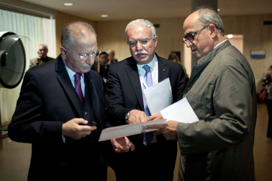 Palestinian Foreign Minister Riad al-Maliki, center, talks with Organization of Islamic Conference Secretary General Ekmeleddin Ihsanoglu, left, and historian and Ambassador for Palestine at UNESCO Elias Sanbar, right, during a session of UNESCO's 36th General Conference, in Paris, Monday Oct. 31, 2011. The U.N. cultural agency is weighing a request to admit Palestine as a full member, a highly divisive bid that's part of the Palestinians' broader push for greater international recognition. (AP Photo/Thibault Camus) / AP