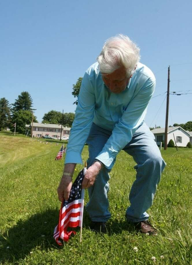 Jim Stull, 78, a life long resident of Thurmont, Md, places American flags along the exit ramp from Route 15 to Route 77 on Thursday, May 17, 2012 in Thurmont, Md. The ramp will be the main travelway for dignitaries motorcading to Camp David for the G8 Summitt. Thurmont, a small mountain town near Camp David, is bracing for the expected arrival of demonstrators bent on disrupting a weekend meeting at the presidential retreat of leaders of the Group of Eight leading industrialized nation.(AP Photo/Timothy Jacobsen)