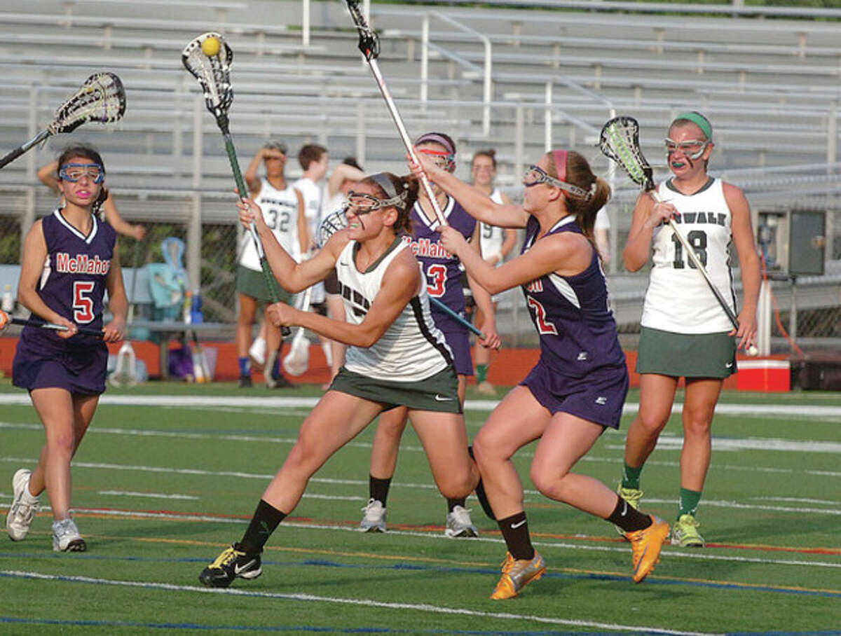 Hour photo/Alex von Kleydorff Norwalk's Thenya Taiyanides, center, scores a goal despite the efforts of a gang of Brien McMahon defenders during Wednesday night's game at Testa Field. Taiyanides scored four goals in the Bears' 17-11 victory -- their first ever against McMahon.
