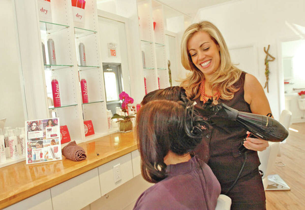 Clarissa Piasuz, stylist at Dry, a blow dry bar in Southport works with a client. Hour photo / Erik Trautmann