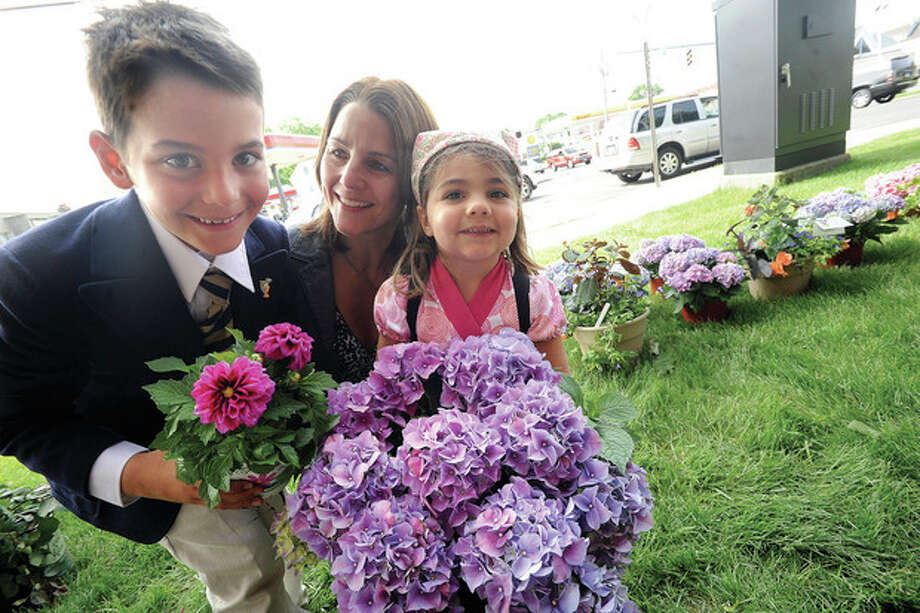 Donna Bonato with her son Lorenzo Zullo 7 and daughter Francesca 3, picking up Mothers Day flowers from Izzo's Country Gardens of Westport who were set up Sunday on the grounds of St. Thomas Church in Norwalk. hour photo/Matthew Vinci