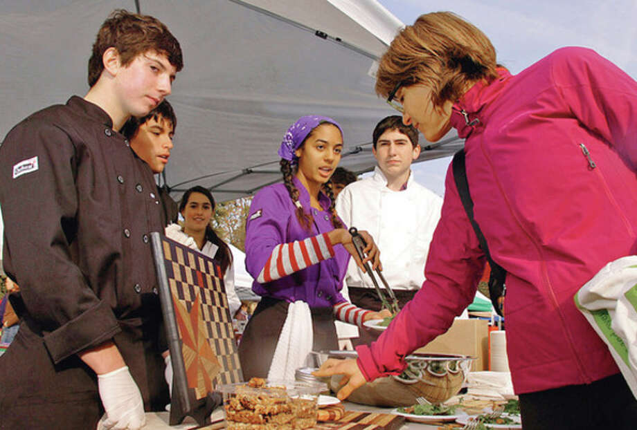 Staples High School culinary students Rusty Schindler, Sebastian Salgado, Kelly Poweres and Rory Siegel serve up salad with Thai dressing to Westport resident Cathy April at the Westport Farmers Market last year.Hour photo / Erik Trautmann / (C)2011, The Hour Newspapers, all rights reserved