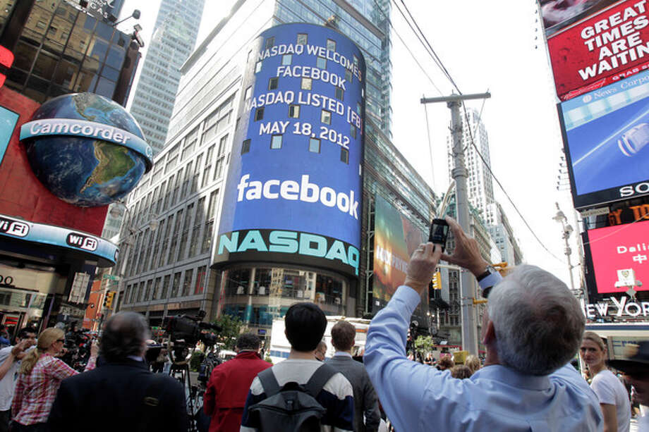 A man stops to photograph Nasdaq in Times Square as Facebook has its IPO, Friday, May 18, 2012, in New York. The social media company priced its IPO on Thursday at $38 per share, and beginning Friday regular investors will have a chance to buy shares. (AP Photo/Richard Drew) / AP